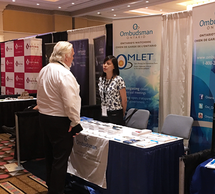 Photo of a conference attendee visiting the Ombudsman Ontario booth